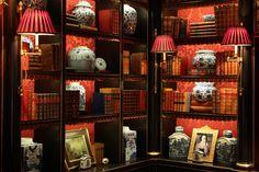 Red damask lined bookshelves, red sconce shades, blue and white porcelain - Alidad Design