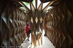 A visitor views houses made of cardboard by Chongqing University students, May 20, 2013.