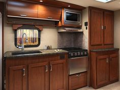 Gallery - Lance 2295 Travel Trailer - Standard exterior kitchen and available interior fireplace set the 2295 apart Truck Bed Camper, Popup Camper, Brown Wood, Dark Brown, Accordion Doors, Fifth Wheel Campers, Fireplace Set, Overhead Storage, Shower Rod