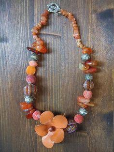 Collana molto particolare con corniola, palline di corallini, metallo anticato, spugna di corallo e...fiore di cuoio.