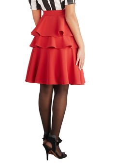 Red knee-length lined flared skirt with faux-wrap front panel, deep flounce at front hem, 2 rear tiered flounces, and wide waistband at natural waist with side zipper and skirt hook. 96% polyester/4% spandex, from ModCloth, $69.99