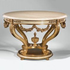 "Louis XVI style round carved wood table with antiqued goldleaf finish, antiqued ivory trim and Crema Marfil marble top with curved, beveled edge; 47½"" x 32″ h. Handmade in Italy.Free Ship"