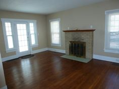 Living room with working wood fireplace and 88-year old refinished wood floors.