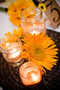 I like the idea of having the biggest mason jar with daisies and two tiered mason jars with candles.
