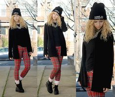 Notes: Plaid pants rolled up at the bottom to a platform spiked black sneaker. Long black cardigan over short black shirt with silver spiked necklace.