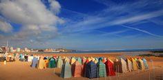 Playa San Lorenzo  San Lorenzo es es la central, santo y seña de Gijón y el principal de sus símbolos naturales. Tres mil metros lineales de arena fina y blanca en medio de la ciudad. Su imagen está asociada al mar de casetas multicolores que ocupan el arenal en verano.
