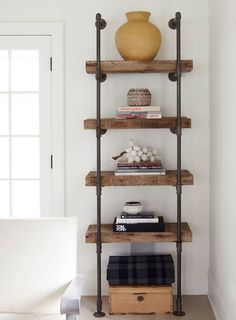 An industrial-style bookcase made of reclaimed wood and plumbing piping adds warmth to the room's whitewashed color scheme.