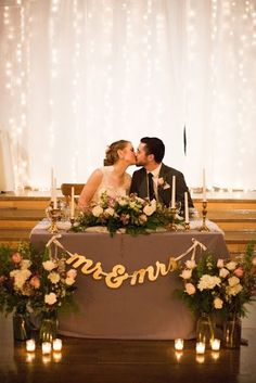 www.theromantictourist.com | Stunning and elegant January winter barn wedding close to Salem, Oregon. Mr & Mrs sweetheart table with twinkle light backdrop and bride and groom kiss