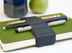 Journal Bandolier - A leather strap fitted with small loops for carrying pens, pencils, and other handy tools wrapped around a journal, planner, or other book.