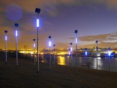 Public art consisting of 12 x 8 metre columns powered by sustainable energy through photovoltaic panels.   Cutting edge radio technology has been used to control the light sequences that use blue and white LED lights to create industrial flashes of light.