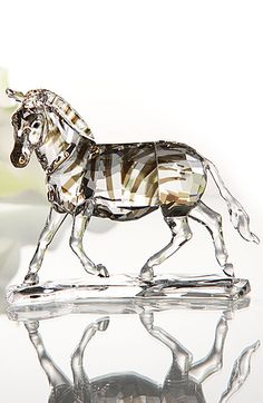 "Swarovski Crystal Zebra   $420.00 	4 15/16"" 		  Item# 1050853 	  	  	   Inspired by the zebra in its natural habitat and showing incredible attention to detail, this exquisite decoration piece realistically represents the zebra in motion.  The eye-catching stripes are achieved with a Crystal Marron coating and are highlighted beautifully by the animal's clear crystal body."