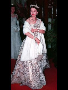 Queen Elizabeth II in high style, her shimmering rose gold one-shoulder gown with floral embroidery, plus a striking tiara and white fur, embodied regal glamour. Hm The Queen, Royal Queen, Her Majesty The Queen, Lady Diana, Young Queen Elizabeth, Elizabeth Taylor, Reine Victoria, Queen Victoria, Mode Chanel