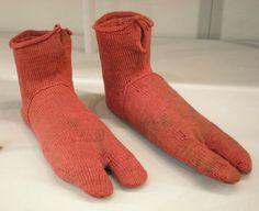 A pair of very, very old red Romano-Egyptian sock made in Egypt sometime between AD 250 and AD 420. They were excavated in the burial grounds of Ancient Oxyrhynchus, a Greek colony on the Nile in central Egypt at the end of the 19th century.