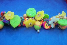 Experimented with translucent polymer to make yellow and green leafs and flower shapes. the other beads are a  scrap clay cane cut into discs.