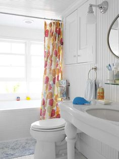 #Coastal white #bathroom #design with vibrant + #colorful #shower #curtain and #cute #accessories.  Would make a great guest or kids #bath!