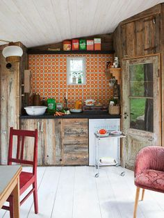 Rustic cabin kitchen with appliances and cupboards covered in reclaimed wood. LOVE THIS
