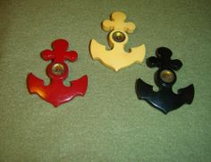 Three large, vintage buttons in shape of anchor, yellow, green and red with a small compass in center of each. The needles in the yellow and green buttons move when tapped, the needle in the red button does not appear to move. These measure 2-3/8 inches long x 1-3/4 inch wide at widest part. Compass section is 5/8 inch wide, has metal ring, probably an insert with see-through plastic face. There is a metal hook on the back of each.  SOLD $131.45