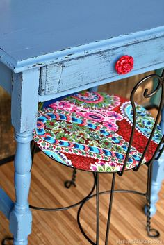 Rose red drawer pull is perfect for the bombshell blue desk. The vintage table was an auction buy and it was a mess. A little love and now it shines. The chair is a purchase from the Nashville Flea Market. I spray painted the iron work and recovered the seat in a beautiful paisley print.