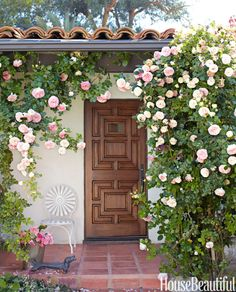 """Eden climbing roses soften the terra-cottafront porch in Chris Barrett's 1929 bungalow in Brentwood. ChrisBarrett designed the oak front door """"to look as if it had always been there.""""   - HouseBeautiful.com"""