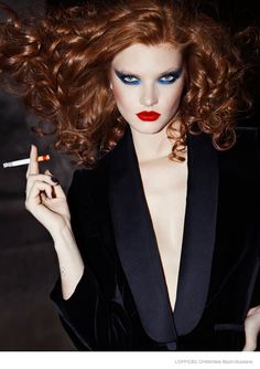 Showing how to make your makeup looks standout at night, the December-January 2015 issue of L'Officiel Switzerland turns up the glam with this fashion editorial photographed by Michèle Bloch-Stuckens. The alluring Anastasia Ivanova poses near the Pont Alexandre III bridge in Paris while wearing bold makeup including blue eyeshadow, rouged cheeks and scarlet red lips. Her red hair is done up in voluminous curls while she models the ...