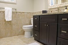 Bathroom design with beige/cream #tile and wainscoat, natural stone backsplash and brown cabinets.