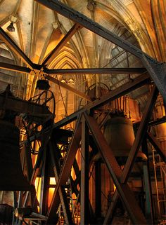 The interior of a bell tower in Cologne, Germany.  Love the contrast of the architecture with the machinery.