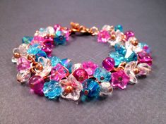 All glass beads on a (9mm link) rose gold tone, copper chain with a toggle clasp. Aqua blue pressed flowers and bicones, hot pink star flowers and orbs, white cup flowers and luster glass rounds, make up this bright bouquet for your wrist. Bracelet fits up to a seven inch wrist (fits