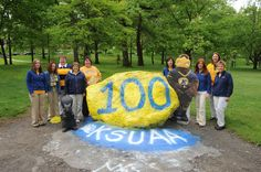 "KSU Alumni Assn staff members at ""the rock"" on the Front Campus: Kent State University main campus in Kent, Ohio. Photo by Jeff Glidden, May Kent Ohio, Kent State University, Alma Mater, Current Events, The Rock, Poses, History, Heart, Figure Poses"