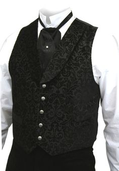 He was ten-fold more dashing in our Bradshaw Embossed Vest than any other gentleman dressed at the annual society affair. Paired with a Frock Coat, Top Hat and Silk Puff Tie, he was dress to the nines in 19th century style.Featuring a tactilely-pleasing black brocade pattern, this men's vest strikes a high note with a formal shawl collar, silvery front buttons and two inset waist pockets. A black belted back allows for an adjustable fit.Fashioned by Wahmaker from 100% cotton with a 100%…