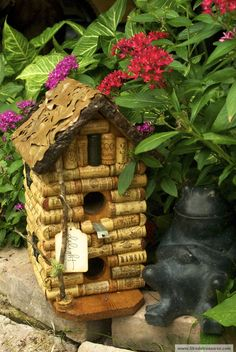 "This unique 2-story condo birdhouse is first made of cedar then covered in upcycled cork in a log cabin pattern, equipped with ""windows"" or ""closed shutters"" (back) on all sides. The perch is a secured bottle opener and the roof is layered in leaves of at least three different trees and trimmed with pine bark for a great natural, camouflaged feel. The front post is secured at the bottom in an abstract cork base with real unaltered moss nestled in the branch and base of the post."