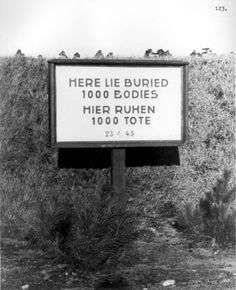 Bergen Belsen death camp, Germany, One of the many mass graves. This mass grave sign states:  1000 dead were buried on 23/04/1945, after the liberation of the camp. Liberators made the ss and town people dig and bury the many 1000's of bodies left laying in piles when liberation of camps were made.
