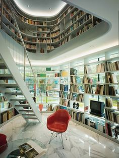 Library with wraparound shelving, marble flooring.