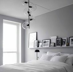 gray and white bedroom with white bedding, natural light, gray walls, funky light fixture, and floating shelf above the bed