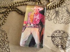What cowgirl wouldn't want to have this handsome cowboy riding shot gun with them? This sexy cowboy is under a 7/8 inch x 1 7/8 inch glass cabochon and he hangs from a 24 inch antiqued brass ball chain. He is sure to be the envy of all your cowgirl friends!!  http://www.thebuckingmare.com/ProductDetails.asp?ProductCode=TBMN812