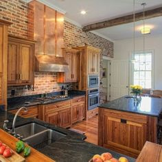 A brick wall kitchen with dark countertops and a large copper range hood.
