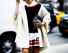 A white dolman cardigan is paired with a crisp white button down, navy blue sweater, and checkered skirt