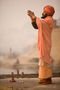 A holy Swami praying beside the river Ganges at Varanasi, India