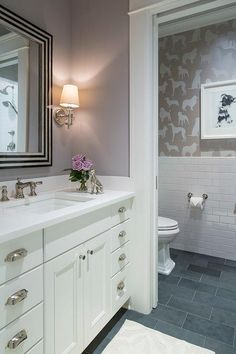 White and gray powder room features an art deco mirror illuminated by Jonathan Sconces placed over an off-white washstand adorned with polished nickel cup pulls topped with white quartz.