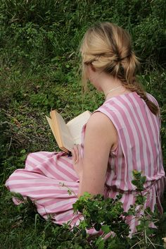 A young girl in a pink striped dress reads her book in a quiet spot in the forest. Photo: Amber. by kimmie-bee, via Flickr