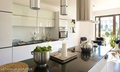 Biała kuchnia jest elegancka i szykowna, a wnętrze ocieplają wilklinowe elementy. Aranżacja białej kuchni z wyspą to udane połączenie nowoczesności z domowym nastrojem. Nowoczesna, biała zabudowa kuchenna z wyspą została ocieplona przez wiklinowe meble i brązowy kolor.