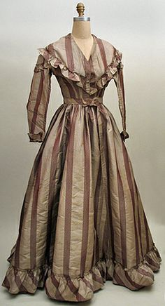 """Circa 1865 gown -- taupe and brown fancy figured silk stripe dress with separate sash. The bodice has dropped shoulders, a ruffled """"V"""", and cuffed sleeves. The skirt has a bias ruffle at the hem. The sash has a small bow at the front and a drape at the center back. The bodice closes with brass hooks & eyes. The neckline has been turned back to form a V, but is intact and could be restored to the original high neckline. The dress is lined through out."""