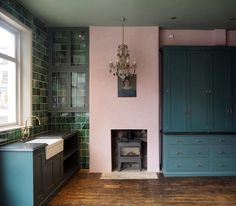 Pink walls in a kitchen with contrasting dark blue kitchen units and green tiles. The antique chandelier and vintage oil painting look unexpected in a kitchen. Dark Blue Kitchens, Dark Green Kitchen, Pink Ceiling, Blue Ceilings, Pink Kitchen Walls, Pink Dining Rooms, Murs Roses, Pink Tiles, Green Tiles