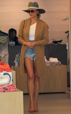 Shady Lady from Chrissy Teigen's Best Looks In jean shorts, an oversized hat and a camel overcoat.