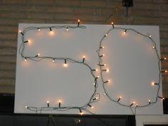 Dubbelzijdig plakband in de vorm van een cijfer en dan kerstlampjes erop.