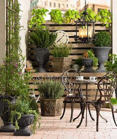 Metal bistro set on brick patio surrounded by plants @Lamps Plus