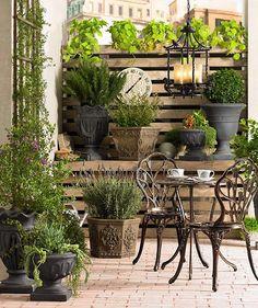 Metal bistro set on brick patio surrounded by plants @Lamps Plus