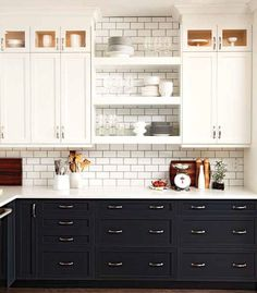 A kitchen with dark bottom cabinets, white upper cabinets, and white subway tile backsplash