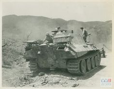 An abandoned Panther Ausf G being looked over by American GI's.