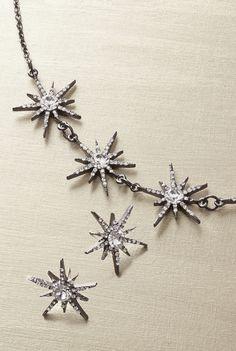 Starburst-shaped crystal stud earrings in silver-toned metal.
