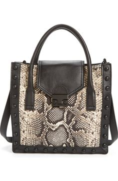 This structured tote adds an edgy yet chic touch to the ensemble with stunning snake-embossed leather and studs.